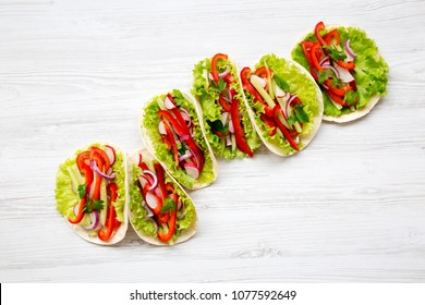 Fresh vegetarian tacos on white wooden background. From above. Top view