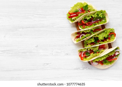 Fresh vegetarian tacos on wooden board on white wooden background. From above. Top view. Copy space