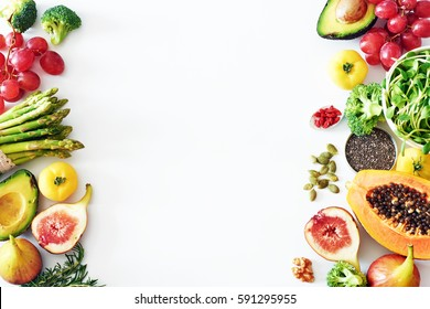Fresh veggies and fruits frame on white background with copy space. Detox or clean-eating concept with avocado, papaya, grape, broccoli, figs, nuts, seeds, superfoods.