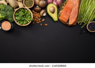 Fresh veggies, salmon fillet top view. Broccoli, ginger, avocado, asparagus, lentils, basil, almonds, beans, berries, mushrooms and onions on black background with copy space.