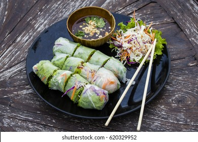 Fresh vietnamese spring rolls on a plate with salad, close up