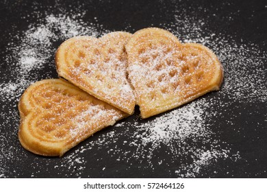 fresh waffles in heart shape with powdered sugar on black background