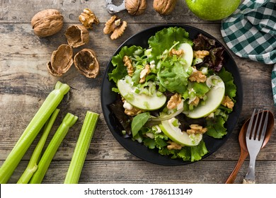 Fresh Waldorf salad with lettuce, green apples, walnuts and celery on wooden table. Top view