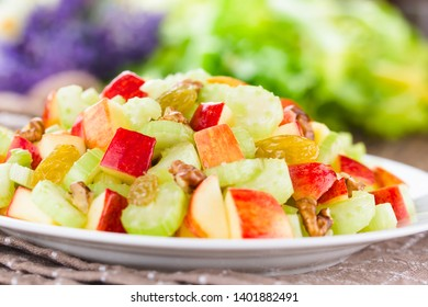 Fresh Waldorf salad made of celery, apple, walnuts, sultanas and raisins on plate (Selective Focus, Focus in the middle of the image)