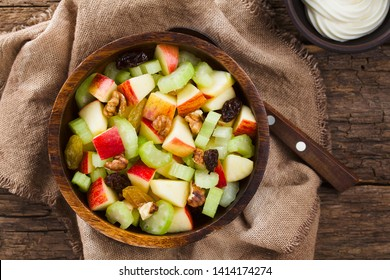 Fresh Waldorf salad made of celery, apple, walnuts, sultanas and raisins in wooden bowl with mayonnaise on the side, photographed overhead