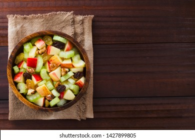 Fresh Waldorf salad made of celery, apple, walnuts, sultanas and raisins in wooden bowl, photographed overhead with copy space on the side