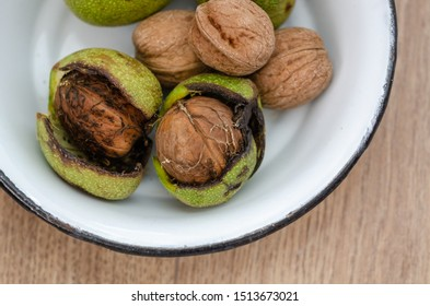 Fresh walnuts with  green shells on a wooden surface. Walnuts, shelled and unshelled,top view.