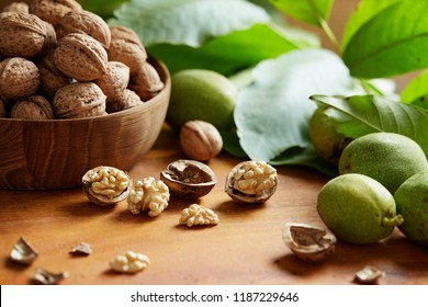 Fresh walnuts with and without shells on a wooden surface. Walnuts, shelled and unshelled.