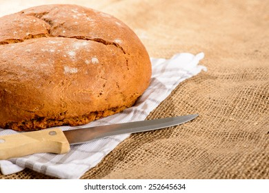 Fresh and warm. Cropped image of freshly baked homemade loaf of bread and knife on a on a farm style sackcloth and a checkered napkin