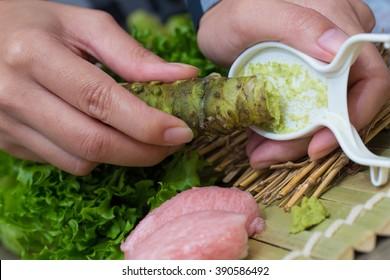 fresh wasabi, a Japanese housewife scraping fresh wasabi root to eat with Nigiri Otoro sushi in the kitchen