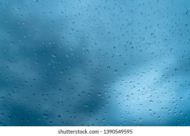 Fresh water drops after raining on blue glass window background in car.
