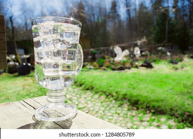 Fresh water in the glass with ice with garden background, horizontal view