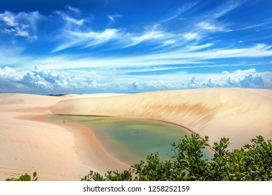 A fresh water lagoon with green vegetation in the foreground in Lencois Maranhenses in northern Brazil