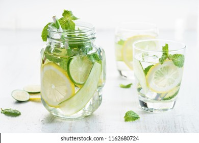 fresh water with lemon, cucumber and mint on white wooden background