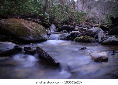 Fresh Water River with Slow Shutter Speed Photography and Rocks with Moss and Lichen.