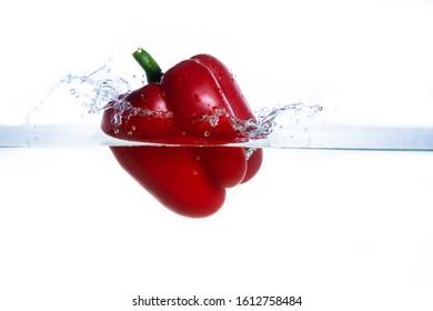 fresh water splash on red sweet pepper isolated on white.