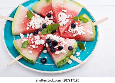 Fresh watermelon popsicles with blueberries and cheese cut on ice