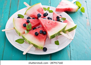 Fresh watermelon popsicles with blueberries cut on ice