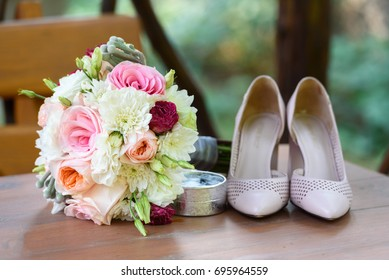 Fresh wedding bouquet near  box with rings and bride shoes in blur on wooden background closeup. Wedding details outdoor. Bouquet and beige bridal shoes. Wedding morning preparation