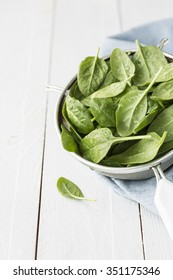 Fresh wet baby spinach leaves in a sieve on white planked wooden table. Preparing food in the rustic kitchen. Layout with free text space.
