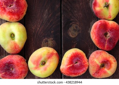 Fresh wet donut saturn peaches on rustic wooden background, center copy space