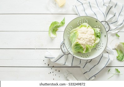 Fresh wet raw cauliflower in a strainer on rustic white wooden background. Preparing meal - rural kitchen scenery from above (flat lay, top view). Layout with free text space.