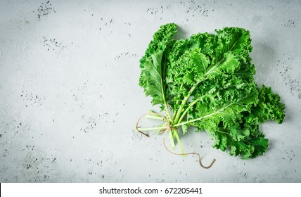Fresh wet raw green kale leaves bunch captured from above (top view, flat lay). Grey stone worktop as background. Layout with free text (copy) space. Superfood - healthy diet theme.