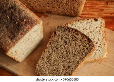 fresh wheat bread coarsely on a cutting Board in the foreground cut off a piece of rye bread lying on a piece of white, top view, vegetarian food, healthy lifestyle, on a yellow background