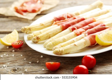 Fresh white asparagus wrapped in jamon on a grey wooden table