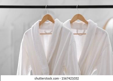 Fresh white bathrobes hanging on rack indoors