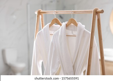 Fresh white bathrobes hanging on rack indoors