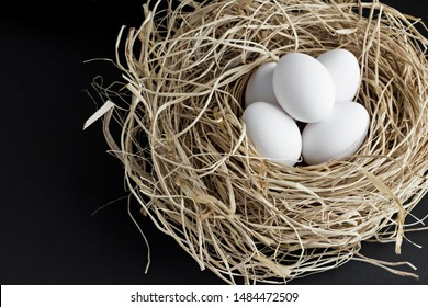 Fresh white eggs in the natural nesting box on the black surface.Creative design.