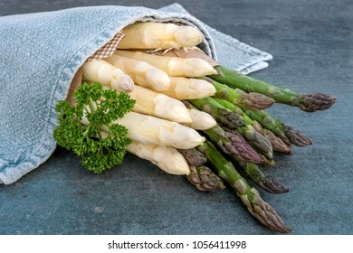 Fresh white and green asparagus with parsley in a towel on a stone plate in a kitchen