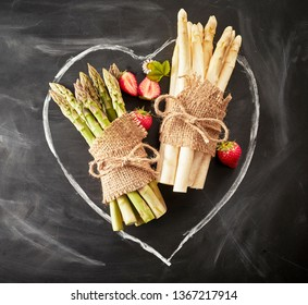 Fresh white and green asparagus tied in bundles with hessian and string inside a hand drawn heart on chalkboard with ripe red strawberries in a conceptual image