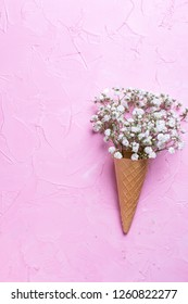 Fresh white gypsofila  flowers in waffle cone on  pink textured background. Top view. Place for text. Vertical iamge.