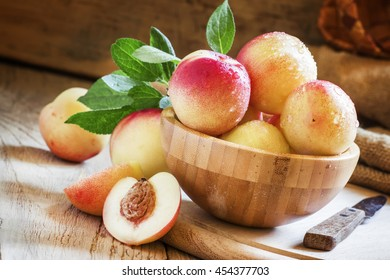 Fresh white nectarines in a wooden bowl, selective focus