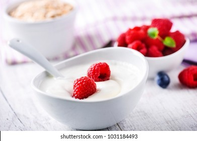 Fresh white yoghurt with raw forest fruits. Rasberries in white yoghurt in bowl on white table. Best meal for healthy breakfast.