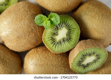 Fresh whole green kiwi fruit and  his slices closeup with mint leaves. Top view