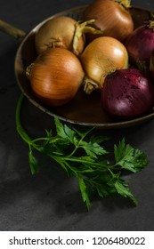 Fresh whole onions in assorted colors and parsley in a small rustic frying pan on kitchen counter top.