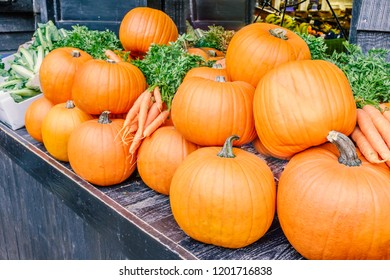 Fresh whole organic orange pumpkins on a stall along side some fresh carrots ready for sale.