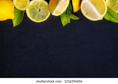Fresh whole and sliced lemons with green leafs on dark stone background, top view, horizontal composition