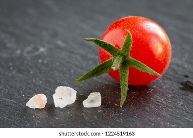 fresh wild currant tomato closeup isolated on a slate plate with copy space and salt crystals