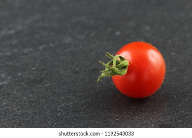fresh wild currant tomato isolated on a slate plate with copy space