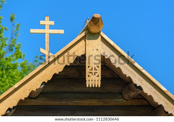 78e312824955 Fresh wood decorative carved fascias and wooden cross on log chapel gable.