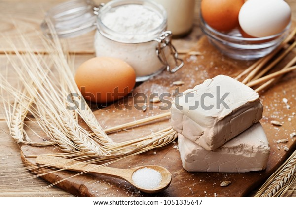 Fresh yeast and ingredients for Easter baking on rustic kitchen background.