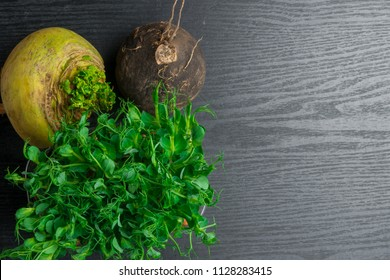 fresh yellow and black turnip with green pea tendrils