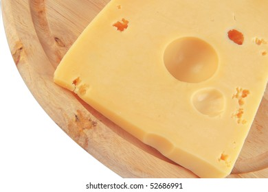 fresh yellow cheese on wooden plate over white