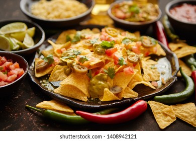 Fresh yellow corn nacho chips garnished with melted cheese, peppers and tomatoes in a handmade ceramic plate on rusty table