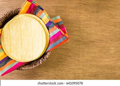 Fresh yellow corn tortillas on a wood background.