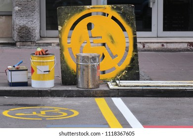 Fresh yellow paint sign on street for disabled parking space